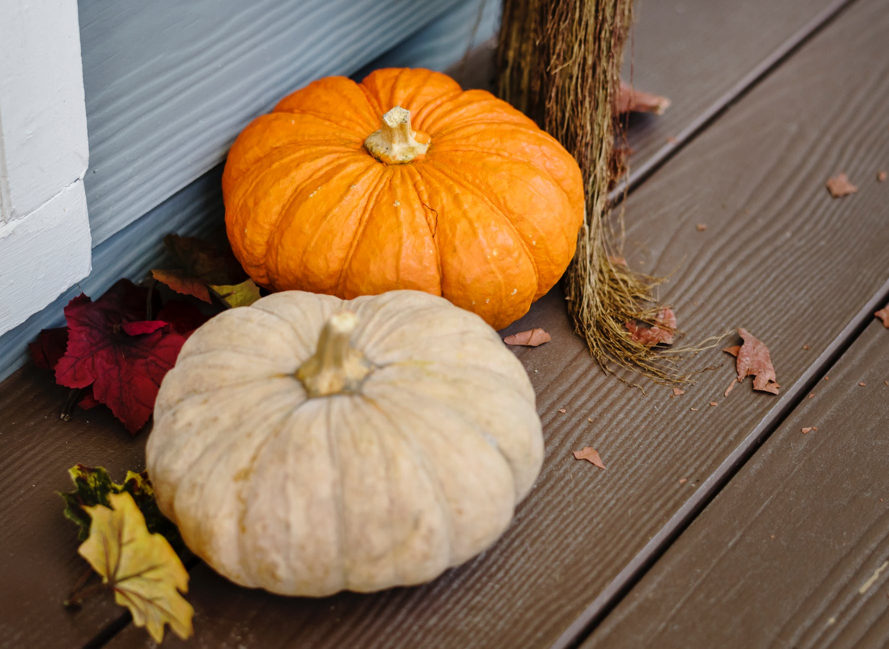 two pumpkins on wooden floor